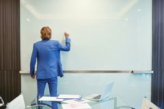 在空白的玻璃委员会的商人后面文字在会议室 免版税库存照片