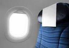 在空白的窗口飞机旁边的蓝色位子 图库摄影