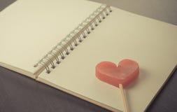 在空白的笔记本日志的心脏在黑桌上 库存照片