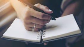 在空白的笔记本的妇女文字在床上早晨 免版税图库摄影