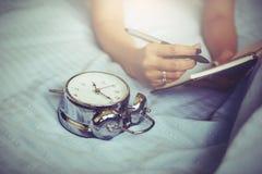 在空白的笔记本的妇女文字在床上早晨 免版税库存照片
