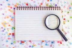 在空白的笔记本的放大镜有字母表信件的成串珠状ba 库存图片