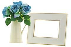 在空白的米黄木画框旁边的黄色陶瓷水罐花瓶 图库摄影
