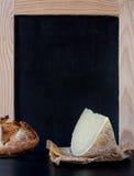 在空白的老黑板菜单前面的软干酪楔子 库存图片