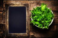 在空白的葡萄酒板岩粉笔板的新鲜的绿色莴苣沙拉 图库摄影