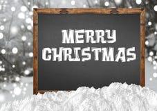 在空白的黑板的圣诞快乐有blurr森林和雪的 库存照片