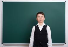在空白的黑板背景附近的小学男孩,穿戴在经典黑衣服,一个学生,教育概念 免版税库存图片