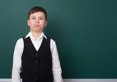 在空白的黑板背景附近的小学男孩,穿戴在经典黑衣服,一个学生,教育概念 库存图片