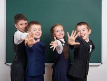在空白的黑板背景附近的小学男孩,穿戴在经典黑衣服,小组学生,教育概念 库存照片