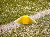 在空白线路的明亮的黄色塑料锥体 有研磨黑色橡胶的塑料橄榄球绿色草皮操场 库存照片