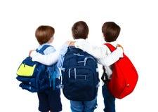 在空白背景查出的三位男小学生 免版税库存图片