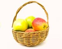 在空白背景查出的篮子的绿色和红色苹果 免版税库存图片