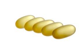 在空白背景查出的黄色半透明的药片 免版税图库摄影