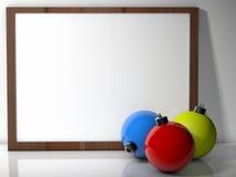 在空白董事会前面的三个圣诞节中看不中用的物品 免版税库存图片