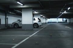 在空的停车库停放的白色汽车 免版税库存图片