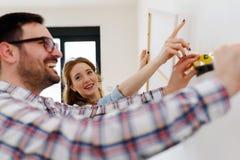 在空的公寓测量的墙壁的夫妇装饰的 免版税库存图片