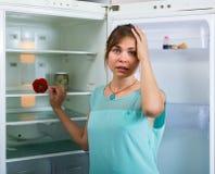 在空的冰箱附近的饥饿的女孩 免版税库存照片