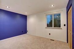 在空的卧室内部的紫色墙壁 图库摄影