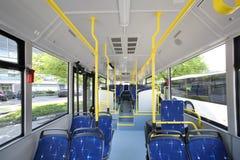 在空的城市公共汽车里面交谊厅的蓝色位子  图库摄影
