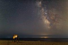 在空的夏天海滩的银河与在前景的救生员椅子 库存照片