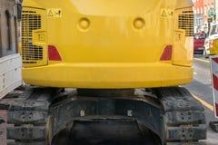 在空的大模型广告时间建筑长跑训练车关闭后的明亮的黄色挖掘机 图库摄影