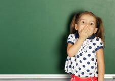 在空的学校黑板附近的微笑的儿童女孩,复制空间 图库摄影