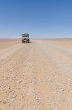 在空的岩石沙漠路的兰德酷路泽4x4向在摩洛哥撒哈拉的尔格Chebbi,非洲 库存照片