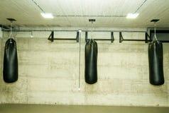 在空的拳击健身房的三个黑沙袋与赤裸难看的东西墙壁在背景中 免版税库存图片