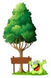在空的木标志旁边的一个愉快的绿色妖怪在下 免版税库存照片