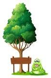 在空的木牌旁边的一个妖怪在树下 免版税库存图片
