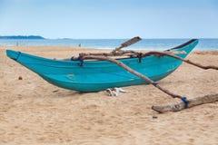 在空的沙滩的传统斯里兰卡的渔船。 免版税图库摄影