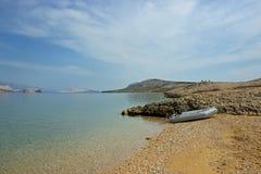 在空的沙滩的汽船在蓝色山海湾 免版税库存图片