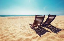 在空的海洋的两张海滩睡椅靠岸在明亮的光亮的太阳下 库存照片