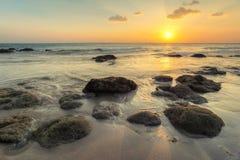 在空的海滩的湿沙子在低潮s期间的金黄日落光 免版税库存照片