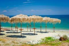 在空的海滩的里德伞 免版税库存照片