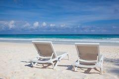 在空的海滩,尤加坦,墨西哥的两张白色海滩睡椅 库存图片