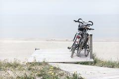 在空的海滩停放的三辆自行车 免版税图库摄影