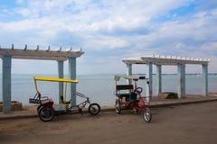 在空的海滩的典型的bicitaxis在日落的Cienfuegoes 免版税图库摄影