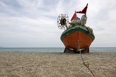 在空的海滩的老渔船 免版税库存照片