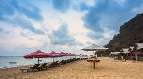 在空的海滩的遮阳伞在日出在巴厘岛 库存图片