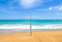 在空的海滩的钓鱼竿与美丽的海洋 转动与匙子诱饵的标尺在海滩的海滩钓鱼竿反对horizo 免版税图库摄影