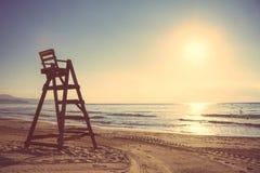 在空的海滩的Baywatch椅子在日落 库存图片