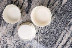 在空的白色杯子蛋糕上的平的位置装入在灰色花岗岩大理石背景的容器 免版税库存照片