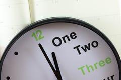 在空的笔记本纸上把放的模式时钟 免版税库存照片