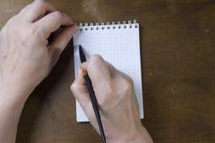 在空的笔记薄的手文字 图库摄影