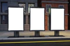 在空的街道上的空白的白色三广告牌在晚上 免版税库存图片
