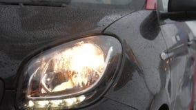 在空的街道的特写镜头黑色现代汽车有眨眼睛车灯的在下雨天 影视素材