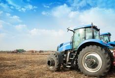 在空的领域的两台蓝色拖拉机 免版税库存照片