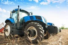 在空的领域的两台蓝色拖拉机 免版税库存图片