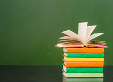 在空的绿色黑板附近打开在堆的书书 文本的样品 库存照片